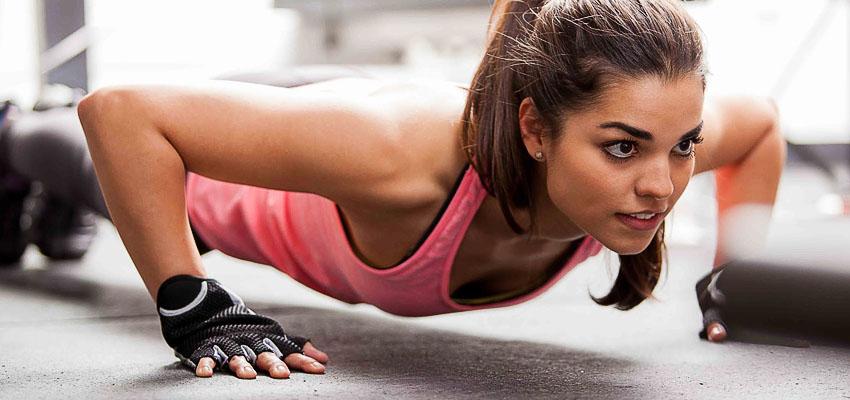 Девушка отжимается в перчатках для фитнеса
